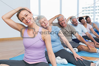 Class stretching neck in row at yoga class