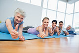 Fitness group gesturing thumbs up at yoga class