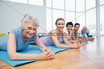 Fitness group lying in row at yoga class