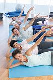 Fitness class stretching legs and hands in row