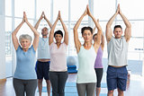 People with eyes closed and joined hands at fitness studio