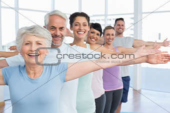 Portrait of fitness class stretching hands in row