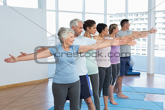 Class stretching hands in row at yoga class