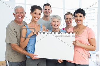 Fit people holding blank board in yoga class
