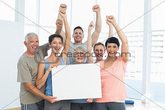 Portrait of happy fit people holding blank board