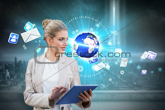 Blonde businesswoman using tablet pc with earth and emails