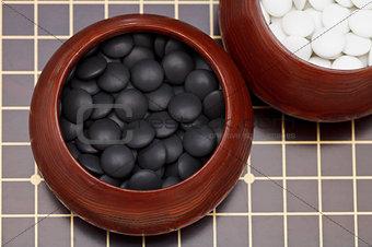 black go stones in wooden bowl on go board