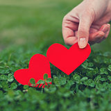 Red paper hearts in green clover