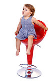 Little toddler girl on red bar stool