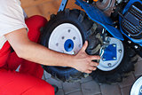 Man mounting tyre on a gasoline motor  tiller