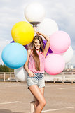 young beautiful lady holding bunch of bright balloons
