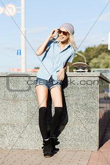Beautiful blonde girl in short shorts with skateboard