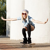 Beautiful blonde girl in short shorts with skateboard