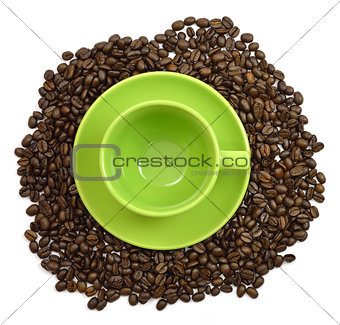 Green cup and saucer in the coffee beans