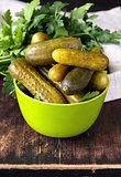 pickled cucumbers in green wooden bowl