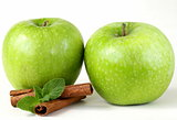 Granny Smith green apples with cinnamon and mint on a white background