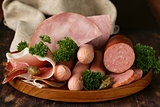 various kinds of sausages and smoked bacon on the wooden plate