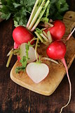 fresh ripe organic radishes on a wooden board