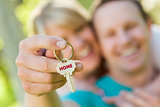 Couple Holding House Key with Home Text