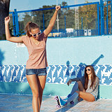 two beautiful young girls wearing sunglasses in an empty pool
