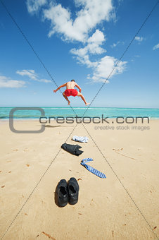 businessman jumping on the beach