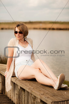 Attractive woman laying next to lake