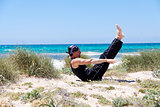 man doing pilates exercises on beach in summer