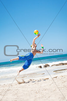 attractive young man playing volleyball on the beach