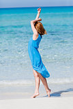 beautiful woman in blue dress on beach in summer