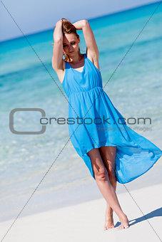 beautiful woman in blue dress on beach in summer