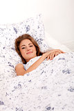 young brunette woman lying in bed sleeping morning