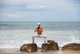 healthy man doing pilates yoga meditation on beach summer