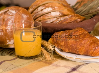 Rustic various baked bread with orange juice