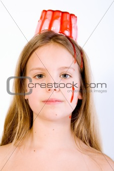 Blond child with desert on her head looking