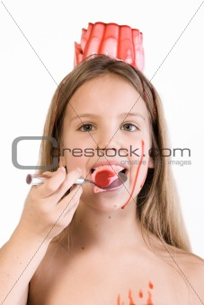 Blond child with desert on her head eating