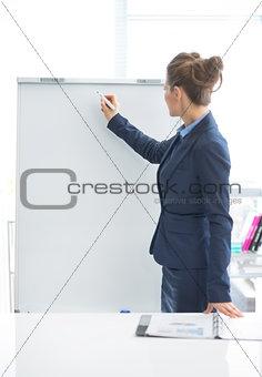 Business woman writing on flipchart