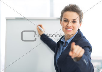 Business woman near flipchart pointing in camera