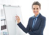 Portrait of happy business woman near flipchart