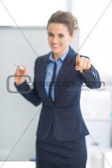 Closeup on business woman near flipchart pointing on listener