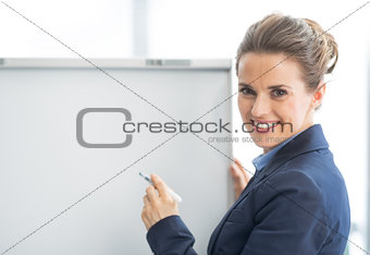 Happy business woman near flipchart