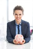 Portrait of happy business woman holding piggy bank