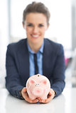 Closeup on happy business woman holding piggy bank