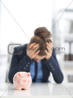 Closeup on piggy bank on table and stressed business woman in ba
