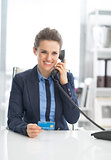 Happy business woman with credit card talking phone