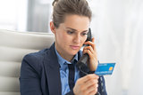 Business woman with credit card talking phone