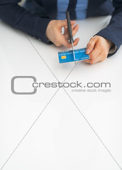 Closeup on business woman cutting credit card with scissors