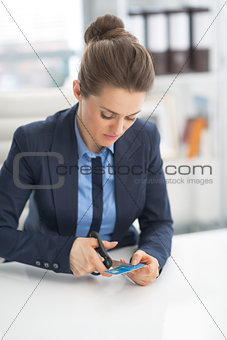 Business woman cutting credit card with scissors