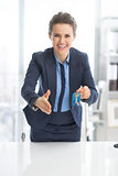 Happy business woman giving keys and stretching hand for handsha