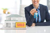 Closeup on happy realtor woman showing keys