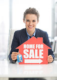 Happy realtor woman showing keys and home for sale sign